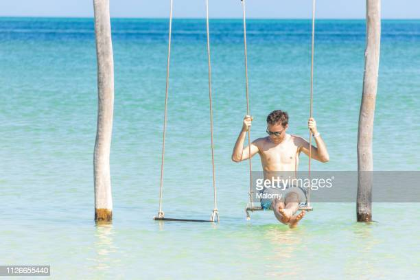young man sitting on a swing in the water at the beach. - holbox island fotografías e imágenes de stock