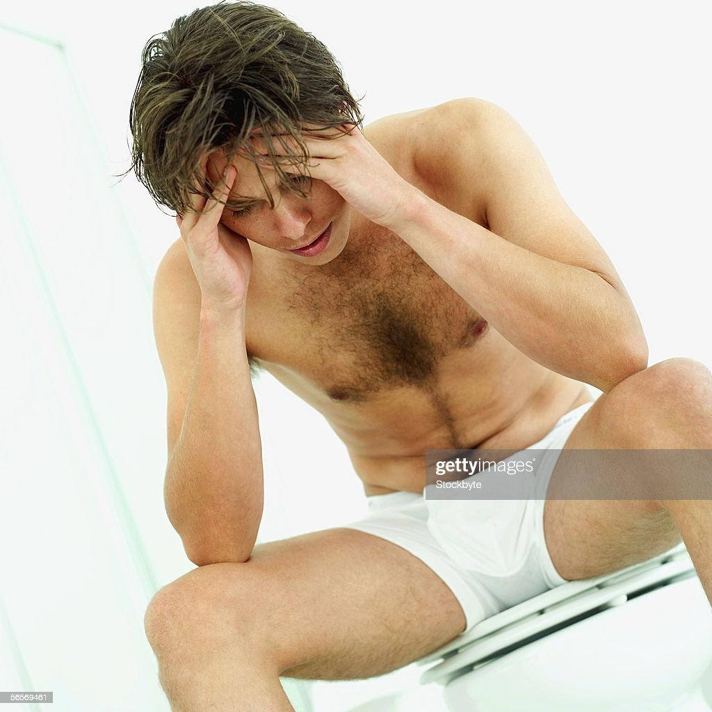 young man sitting on a toilet seat holding his head : Stock Photo