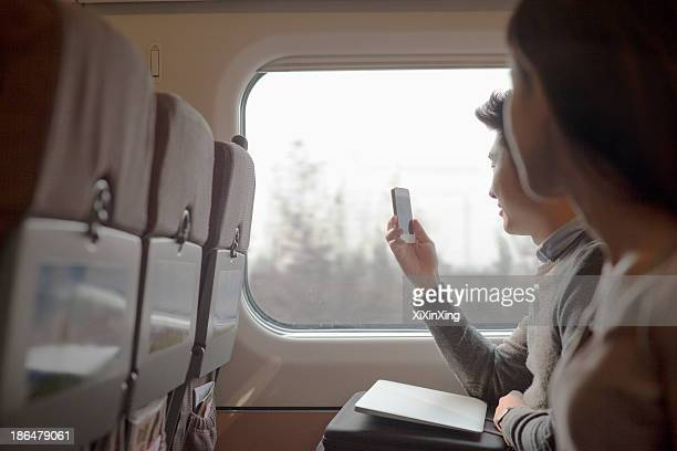 Young man sitting on a train taking a photo out the window
