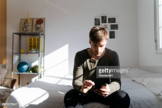 young man sitting on bed looking at his smartphone - sadness stock pictures, royalty-free photos & images