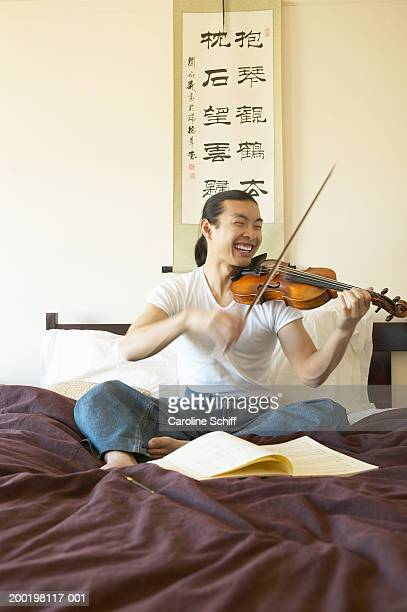 Young man sitting on bed, playing violin, smiling
