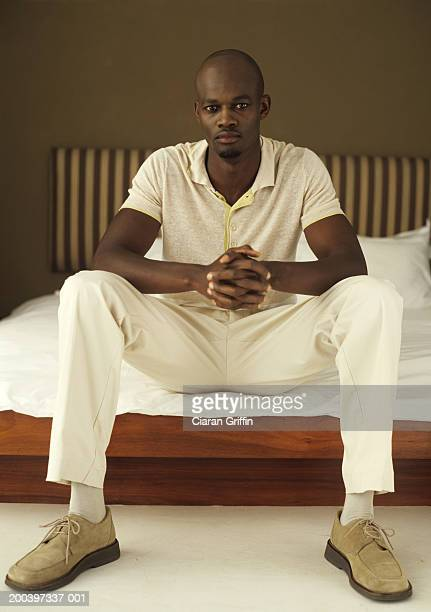 young man sitting on bed, portrait - benen gespreid stockfoto's en -beelden