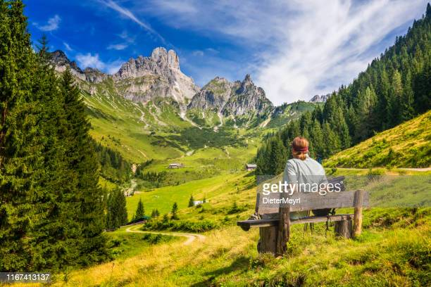 young man sitting on bench and enjoys view on big bischofsmütze, dachstein mountains, alps - austria foto e immagini stock