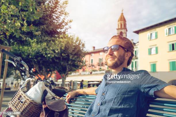 junger mann sitzen auf bank genießen sommer im schweizer dorf - kleinstadt stock-fotos und bilder