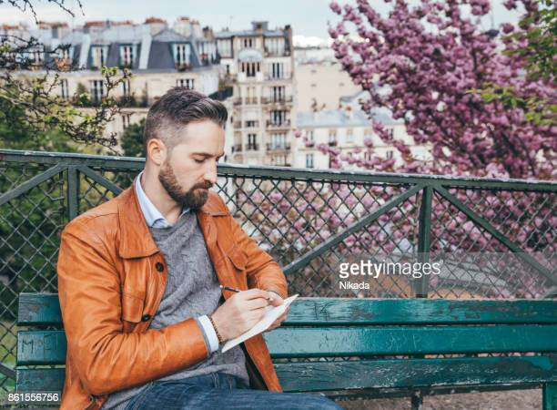 young man sitting on bench with notebook, montmartre, paris - pencil drawing stock pictures, royalty-free photos & images
