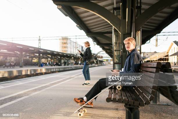 Young man sitting on bench with teenage girl in background at railroad station platform