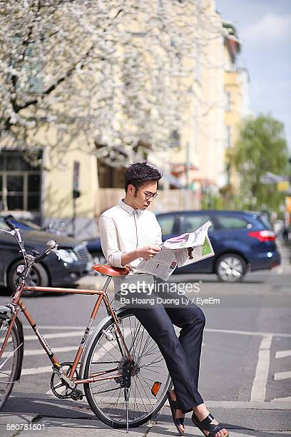 Young Man Sitting On Bicycle While Reading Newspaper