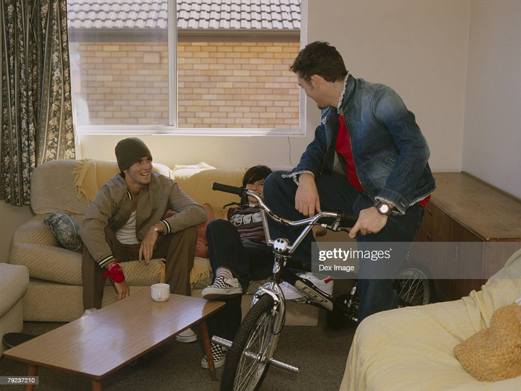 Young man sitting on bike, while friends gather on sofa : Stock Photo