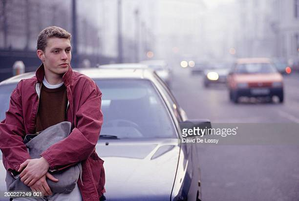 Young man sitting on bonnet of car holding bag
