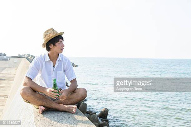 Young Man Sitting On Breakwater