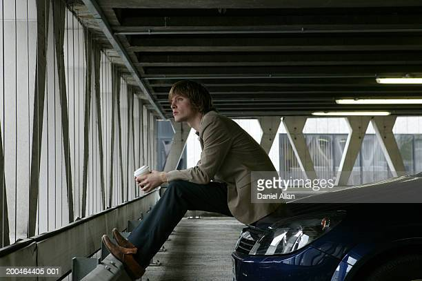 Young man sitting on car bonnet holding paper cup in car park