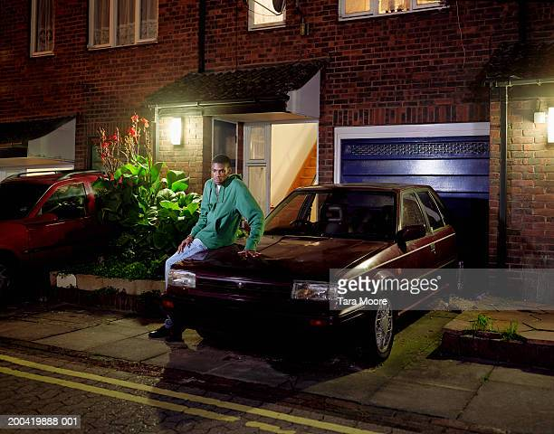 Young man sitting on car outside terraced house