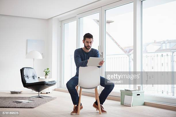 Young man sitting on chair in his living room using digital tablet