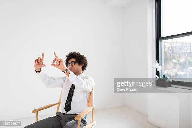 Young man sitting on chair making finger frame