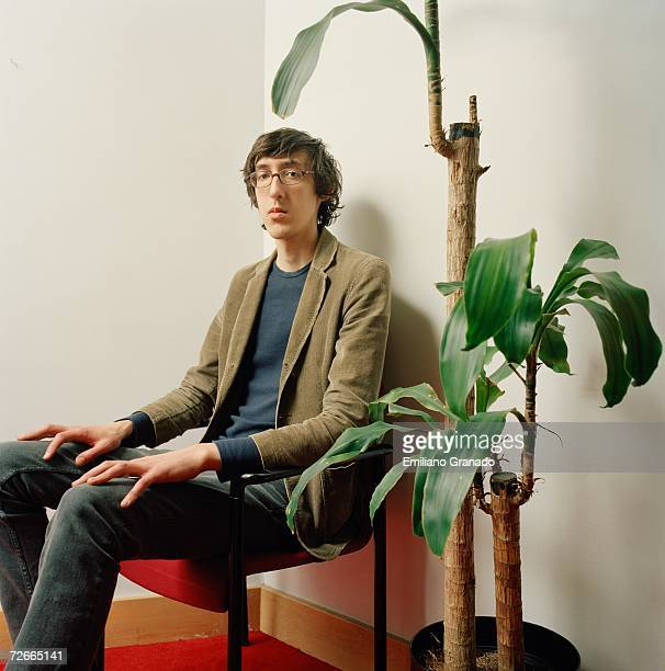 Young man sitting on chair next to potted plant
