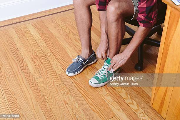 young man sitting on chair trying on two different shoes, low section - ふぞろい ストックフォトと画像