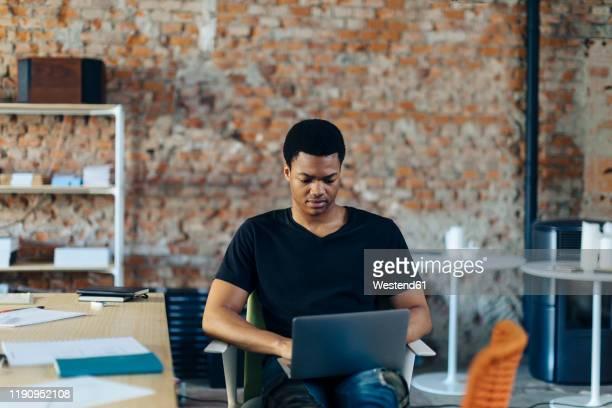 young man sitting on chair using laptop - gründer stock-fotos und bilder