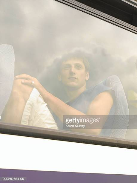 Young man sitting on coach, view through window