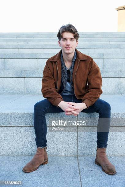 young man sitting on concrete steps. - cultura británica fotografías e imágenes de stock