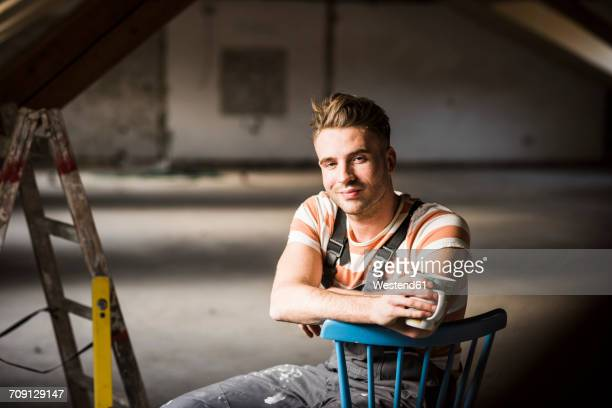 Young man sitting on construction site of his new home