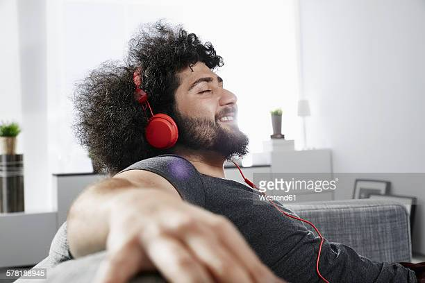 young man sitting on couch at home listening music with headphones - zurücklehnen stock-fotos und bilder