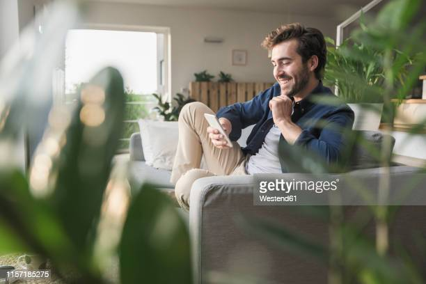 young man sitting on couch at home, using smartphone - contente imagens e fotografias de stock