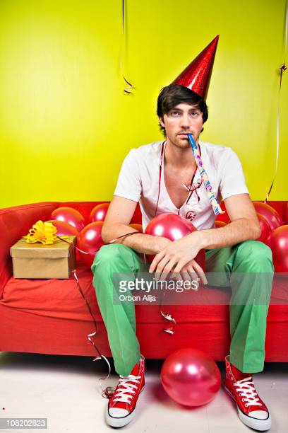 young man sitting on couch celebrating birthday with balloons - after party stockfoto's en -beelden