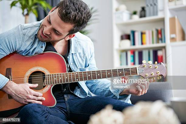 Young man sitting on couch tuning guitar