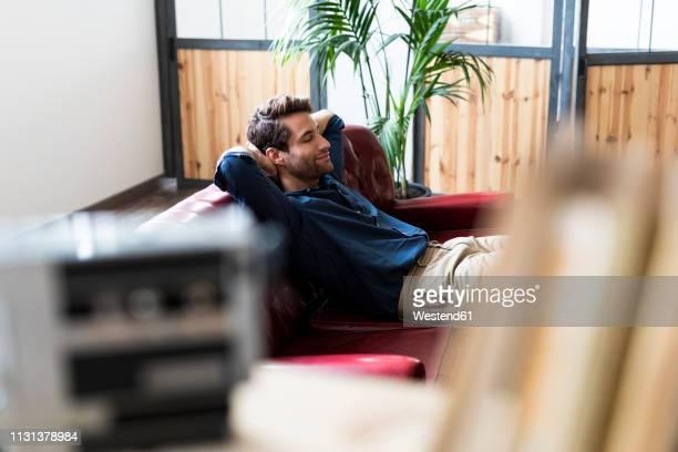 young man sitting on couch with closed eyes - descansar fotografías e imágenes de stock