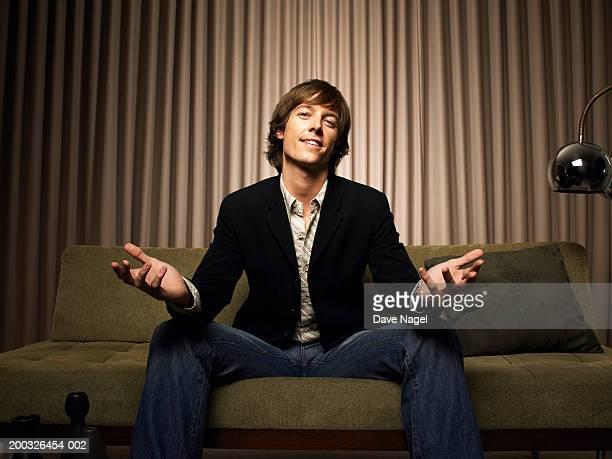 young man sitting on couch with hands outward, portrait - überzeugen stock-fotos und bilder