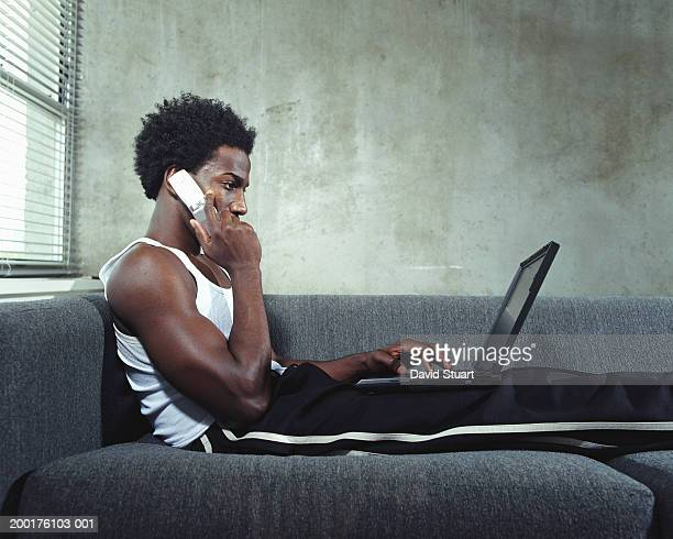 young man sitting on couch with laptop, talking on mobile phone - tracksuit bottoms stock pictures, royalty-free photos & images
