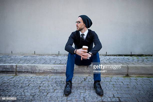 Young man sitting on curb with takeaway coffee