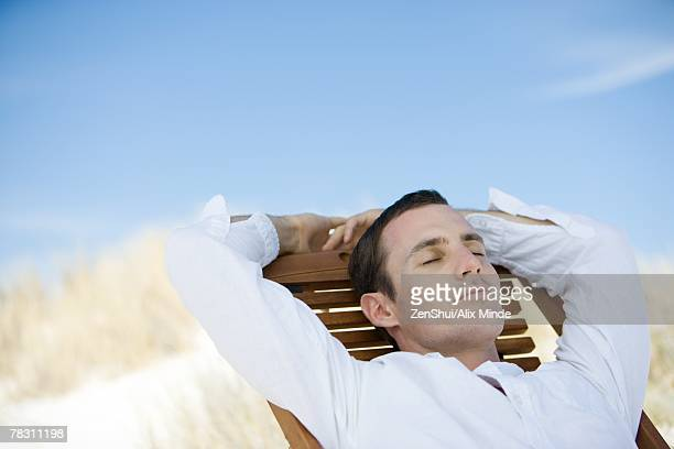 Young man sitting on deckchair, eyes closed