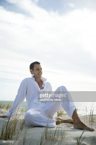 young man sitting on dune, smiling, full length - colletto aperto foto e immagini stock
