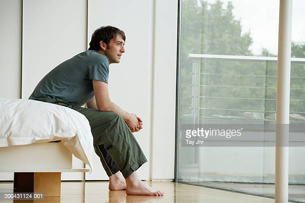 young man sitting on edge of bed, looking out patio doors, side view - ナイトウェア ストックフォトと画像