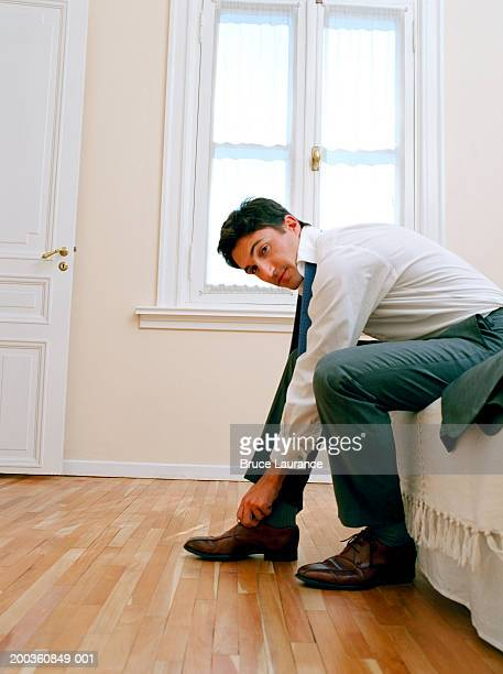 young man sitting on edge of bed, tying shoelace, portrait - tying shoelace stock pictures, royalty-free photos & images