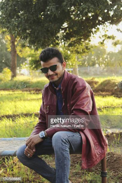 young man sitting on field - una persona stock pictures, royalty-free photos & images