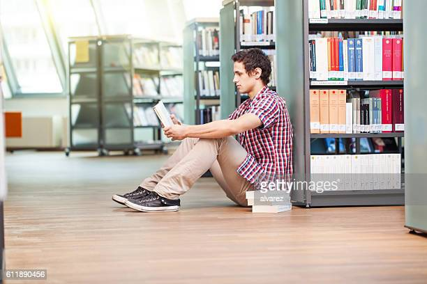 Young man sitting on floor and reading in library
