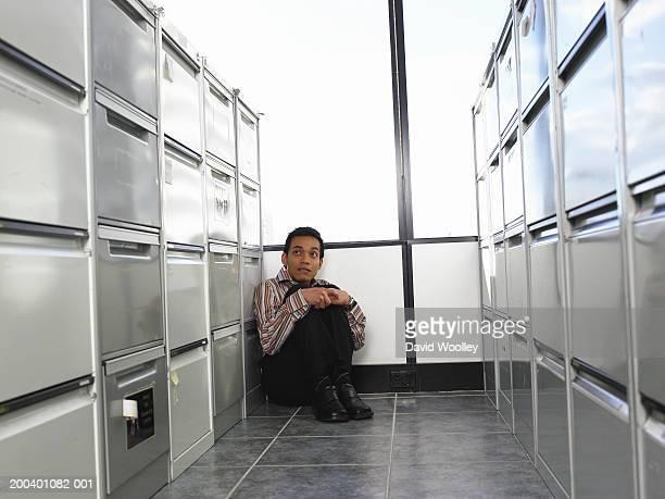 young man sitting on floor between filing cabinets - esconder imagens e fotografias de stock