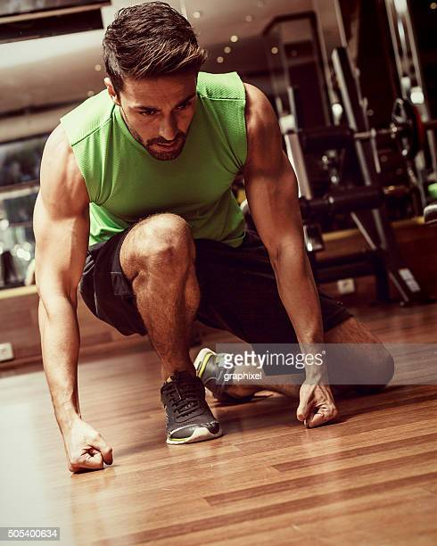 young man sitting on floor in gym - graphixel stock pictures, royalty-free photos & images