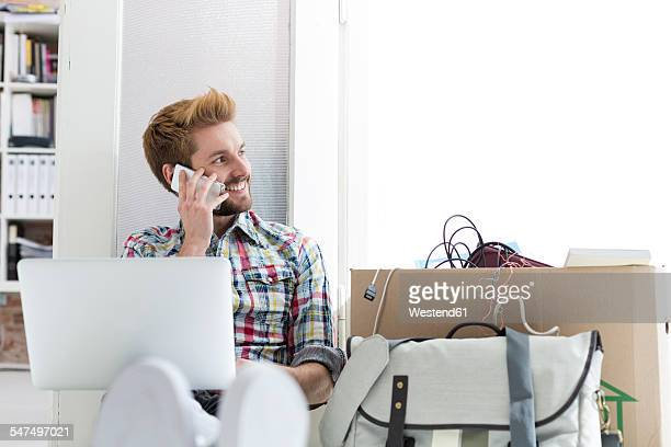 Young man sitting on floor in office using laptop and cell phone