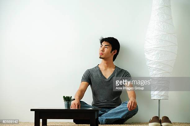 Young man sitting on floor looking up