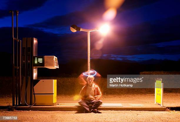 Young man sitting on floor of gas station with halo shape above his head