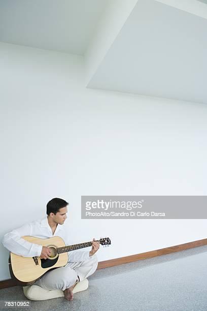 young man sitting on floor, playing guitar, full length - 胡坐 ストックフォトと画像