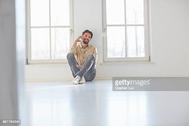 Young man sitting on floor talking on smartphone in empty new home