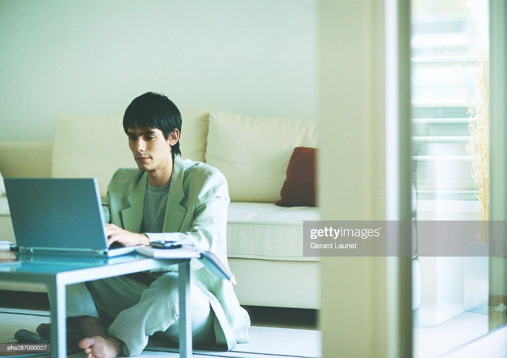 Young man sitting on floor, using laptop on coffee table : Stockfoto