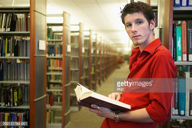young man sitting on footstool between bookshelves in library - open grave stock photos and pictures