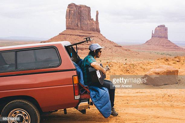 young man sitting on four wheel drive boot playing acoustic guitar, monument valley, arizona, usa - southwest usa stock pictures, royalty-free photos & images