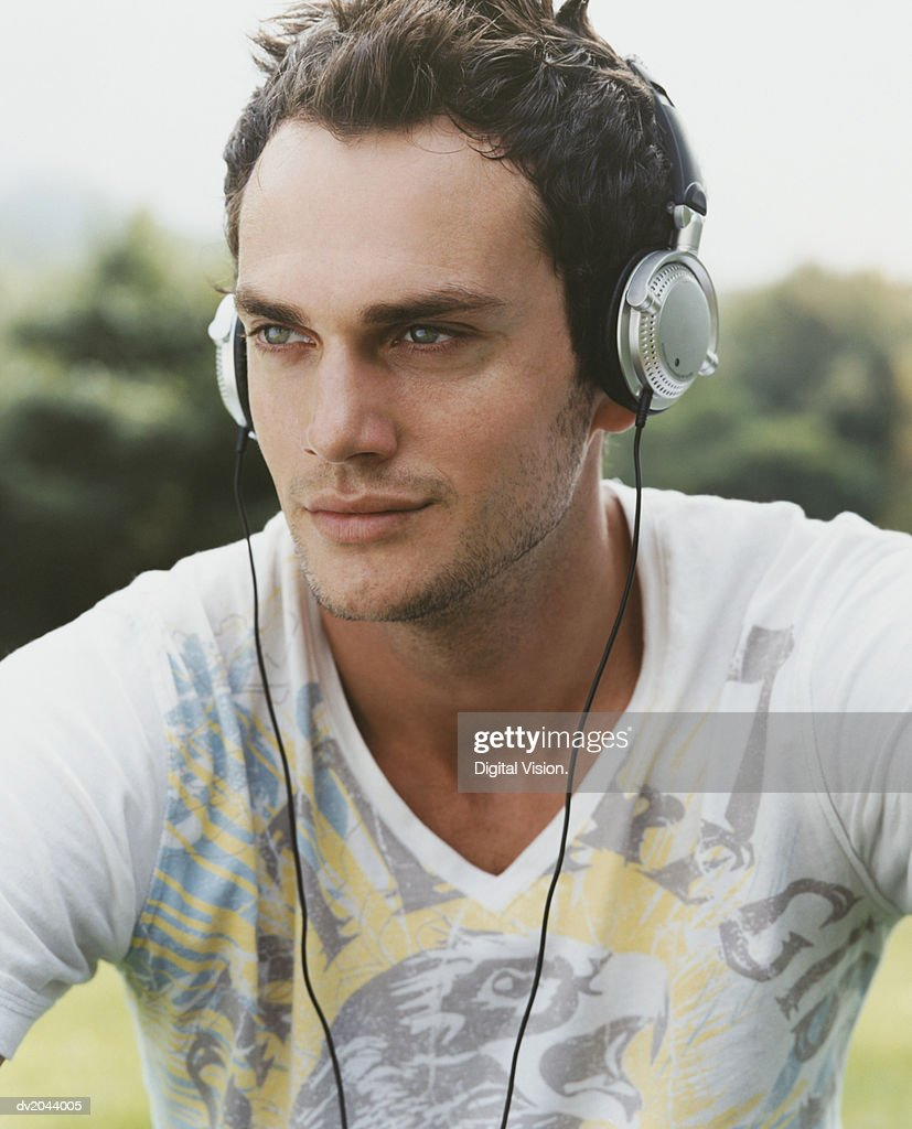 Young Man Sitting on Grass Listening to Music on His Headphones : Stock Photo