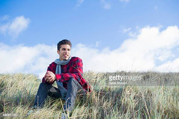 Young man sitting on grass